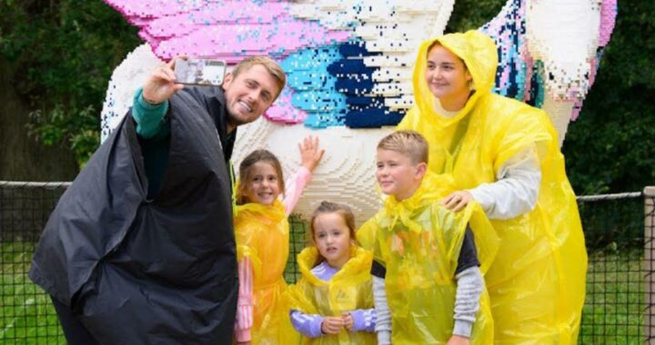 Jacqueline Jossa and Dan Osborne smile in rain coats as they enjoy fun family day out